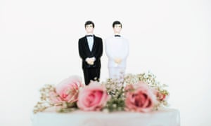 A wedding cake with two men on it
