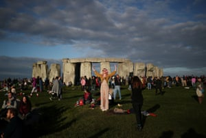 The sun rises as revellers welcome in the Summer Solstice at the Stonehenge stone circle.