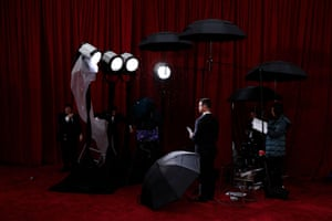 A television producer stays dry as the rain falls on the red carpet.
