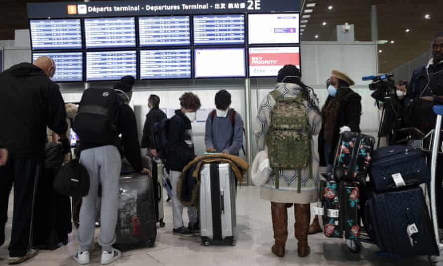 Travellers at Paris Charles de Gaulle airport after the US banned travel from 26 EU countries
