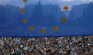 Protesters gather in Athens under an EU flag