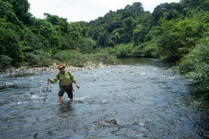 Forest Ranger Nguyen Thanh Huyen crosses a river in the dense Khe Nuoc Trong Forest in Vietnam.