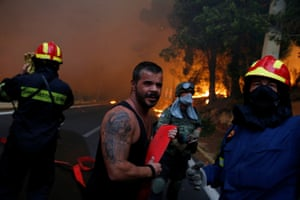 Firefighters, soldiers and local residents carry a hose to battle the blaze in Rafina