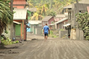 A man walks down an ash-covered street in Georgetown.