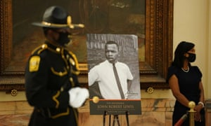 A state trooper stands next to a picture of the late congressman John Lewis in Atlanta