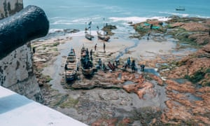 Cape Coast Castle, Ghana. Fishermen tend to their boats on the shores of the castle