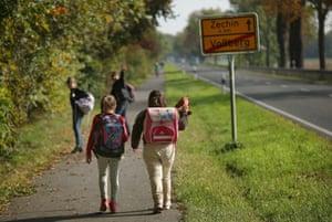 Children walk down a road in Vossberg