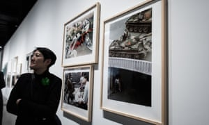 A woman walks past pictures depicting the Tiananmen events by Hong Kong born photographer Liu Heung Shing during the preview of the M+ Sigg art show in Hong Kong.