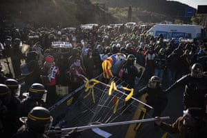 French police officers remove pro-Catalan independence demonstrators blocking a major highway border pass near La Jonquera between Spain and France, 12 November.