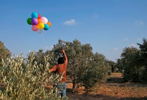 A Palestinian man prepares to release balloon-borne explosive and incendiary devices aimed at Israeli lands near al-Bureij refugee camp