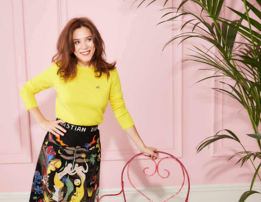 Anna Friel wearing a yellow top and staning beside a chair