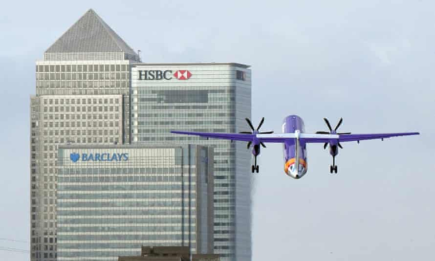 A Flybe plane takes off with the HSBC tower in the background