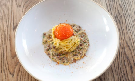 A coil of linguine, topped with egg yolk, in the centre of a large round white bowled plate