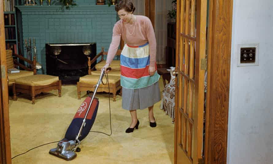 1953 photo of woman vacuuming a living Room.