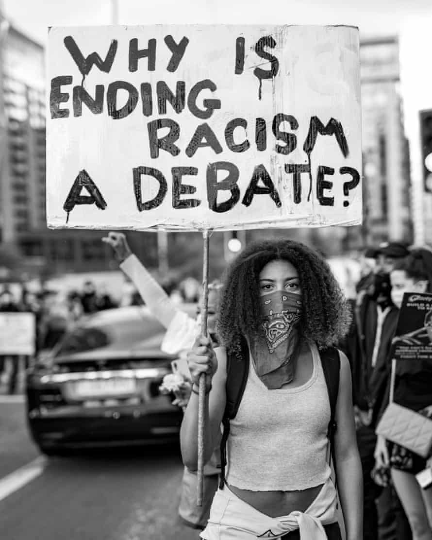 Darcy Bourne, an England under-21s hockey player, with her placard 'Why Is Ending Racism a Debate?'.