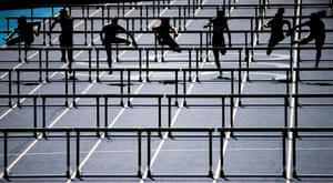 Athletes compete in the heats of the women's 100m hurdles.