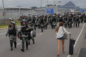 A passenger walks pass riot polices as protestors blocked a road outside the airport in Hong Kong , September 1, 2019.