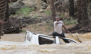 A man tries to save a vehicle being swept away by flood waters in the Yemeni island of Socotra
