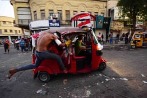 A protester rides a tuk-tuk during clashes with riot police forces near Al-Ahrar bridge in central Baghdad.