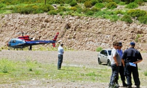 Police standing near a police helicopter after a helicopter shooting a reality TV show crashed in the reservoir at Potrerillos Dam, killing two people.