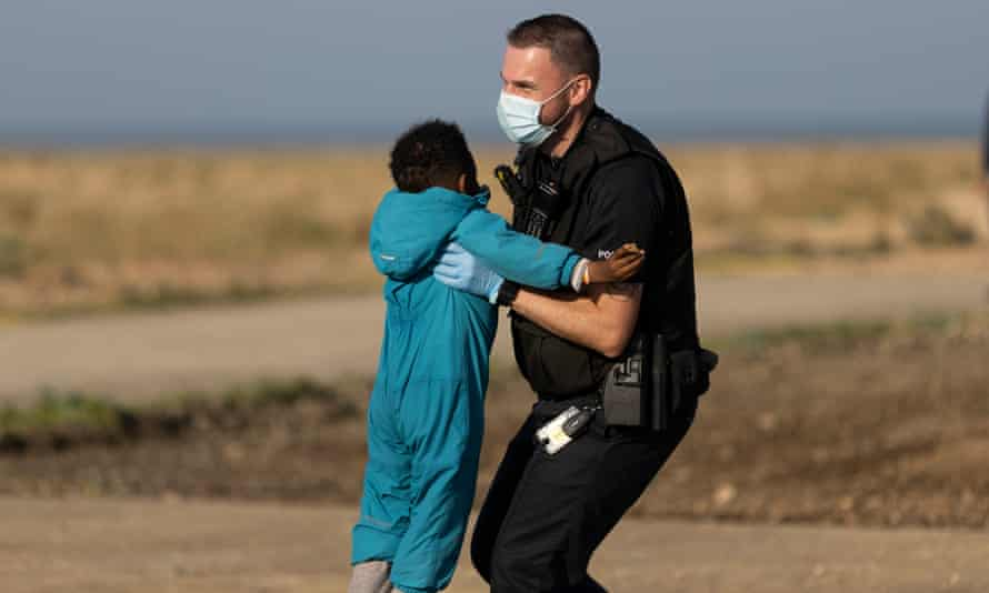 A border Force official carries a child who arrived in England on a small boat this week.