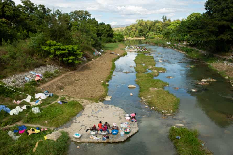 Women wash laundry along the Meille River, a tributary to the Artibonite River, the longest waterway in Haiti, which carried cholera through the country