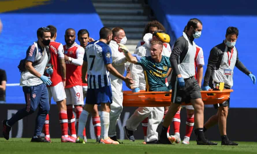 Arsenal's goalkeeper Bernd Leno points the finger at Neal Maupay while being carried off.