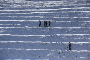 People walk across the snow after a snowfall in Sulaymaniyah, Iraq.