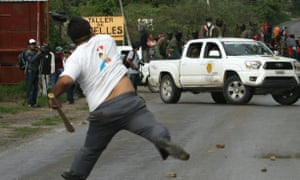 A man throws stones at members of the community police force – who oppose the elections – in Tixtla in Guerrero state.
