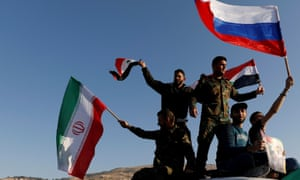 Syrians in Damascus wave Iranian, Russian and Syrian flags during a protest against US-led air strikes