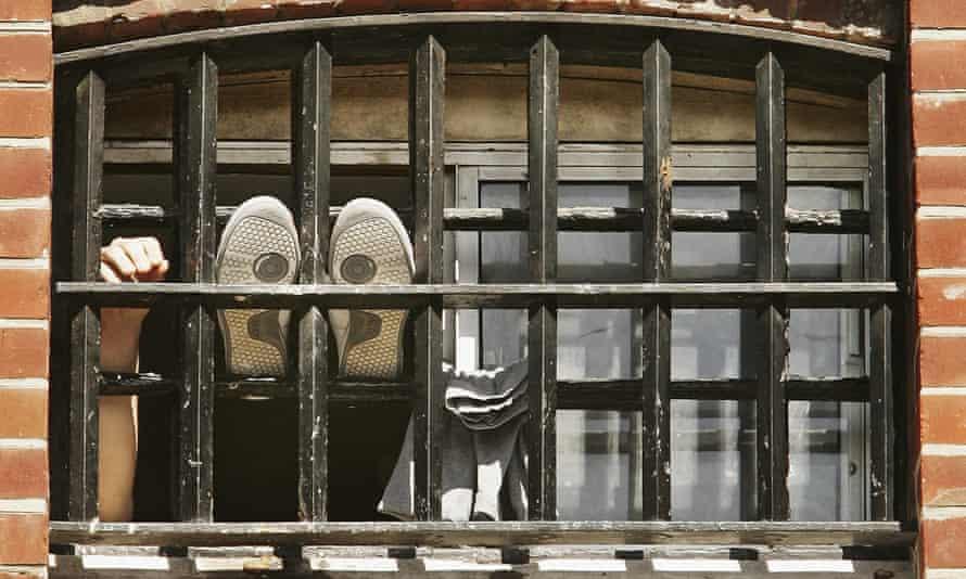 Man sticking feet onto bars of prison window