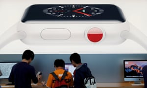 Customers are seen under a picture of new Apple Watch Series 3 after it goes on sale at the Apple Store in Tokyo's Omotesando shopping district, Japan, September 2017.