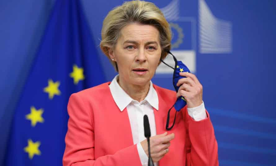 Von der Leyen taking off mask to give an address in front of an EU flag.