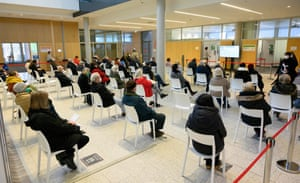 People sit in the waiting area of the Corona vaccination center at the Robert-Bosch hospital in Stuttgart, southern Germany, on 12 February, 2021.