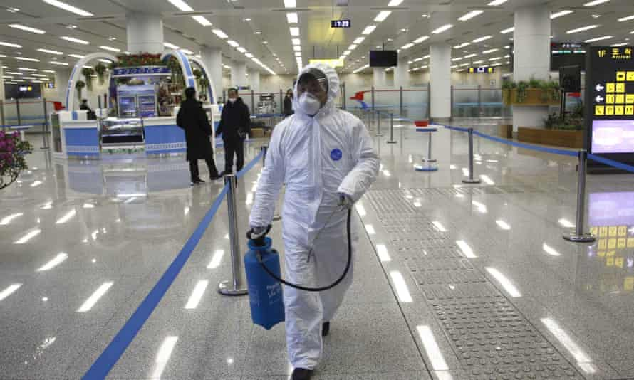 A worker in protective gear carries a disinfectant spray can at the Pyongyang airport.