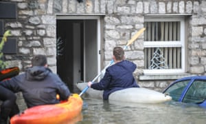 A man canoes straight into his flooded house on Gandy Street in Kendal.