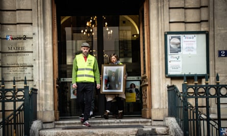 Activists leave with a portrait from a town hall in Lyon.