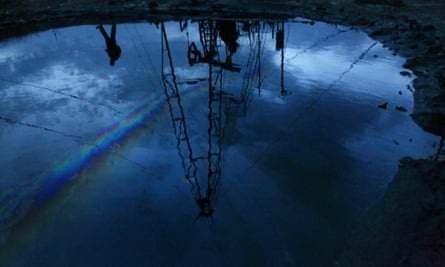 Oil derrick reflected in puddle