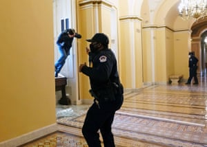 A US Capitol police officer shoots pepper spray at a protester attempting to enter the Capitol building during a joint session of Congress on Wednesday.