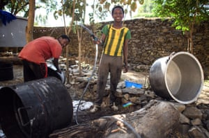 Local boys clean large cooking pots ahead of the festival