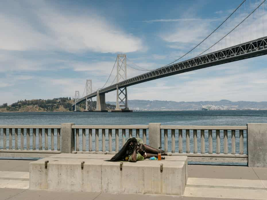 A woman lies on a block along the Embarcadero across from Google's satellite office in downtown San Francisco.