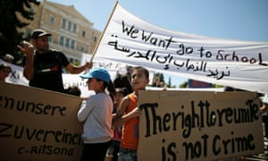 Syrian refugee children hold banners during a protest in Athens against delays in reunifying families.