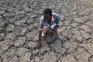 In Zimbabwe's Chivi district, Last Zimaniwa touches the parched ground at a spot that used to be a reliable source of water but has since dried up due to lack of rain