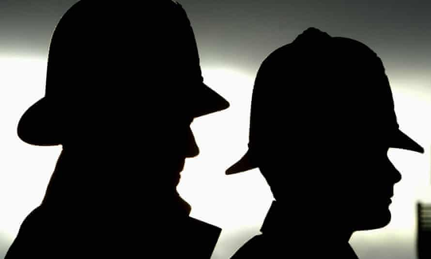 Silhouettes of two UK police officers.