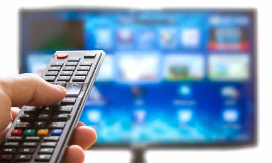 someone watching TV holding a remote control