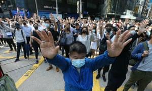 Demonstrators raise their hands during a protest in the financial district in Hong Kong.