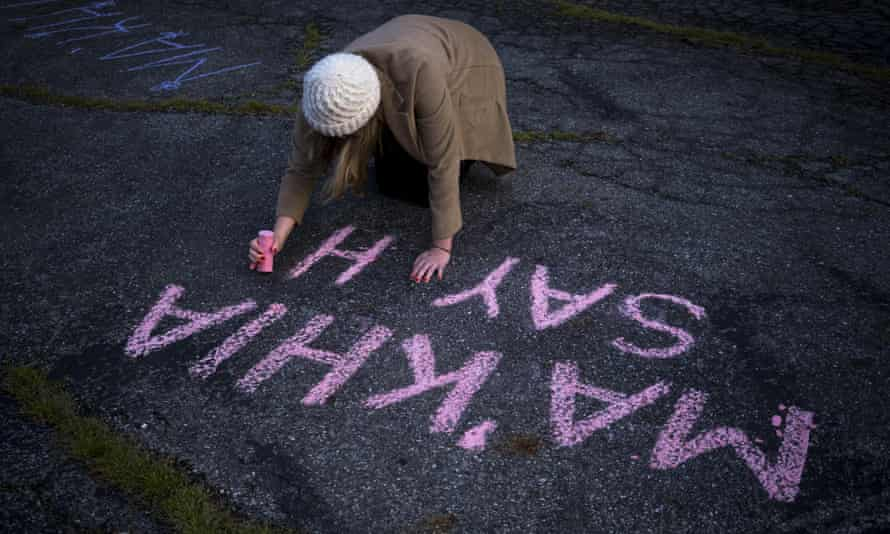 A woman writes Ma'Khia Bryant's name in chalk in Columbus in April.