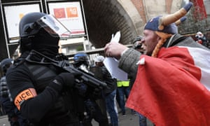 A pensions reform protester dressed as the comic book character Obelix talks to a French policeman in Paris on Saturday 11 January.