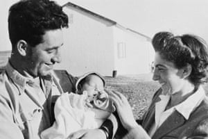 A very young Peres holding a baby and his wife Sonia - both smiling at the baby