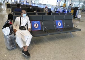 A passenger sits beside posters displaying social distancing restrictions as he waits for his flight at the King Abdulaziz International Airport in Jiddah, Saudi Arabia, on 28 July 2020. The authorities have eased domestic travel restrictions since June.